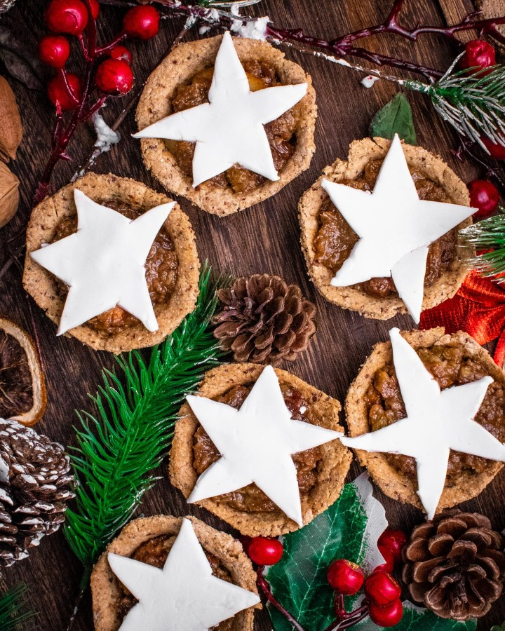 mince pies with fondant icing star shapes on top of each pie on wooden table next to pine tree bits, pine cones and holly bush berries