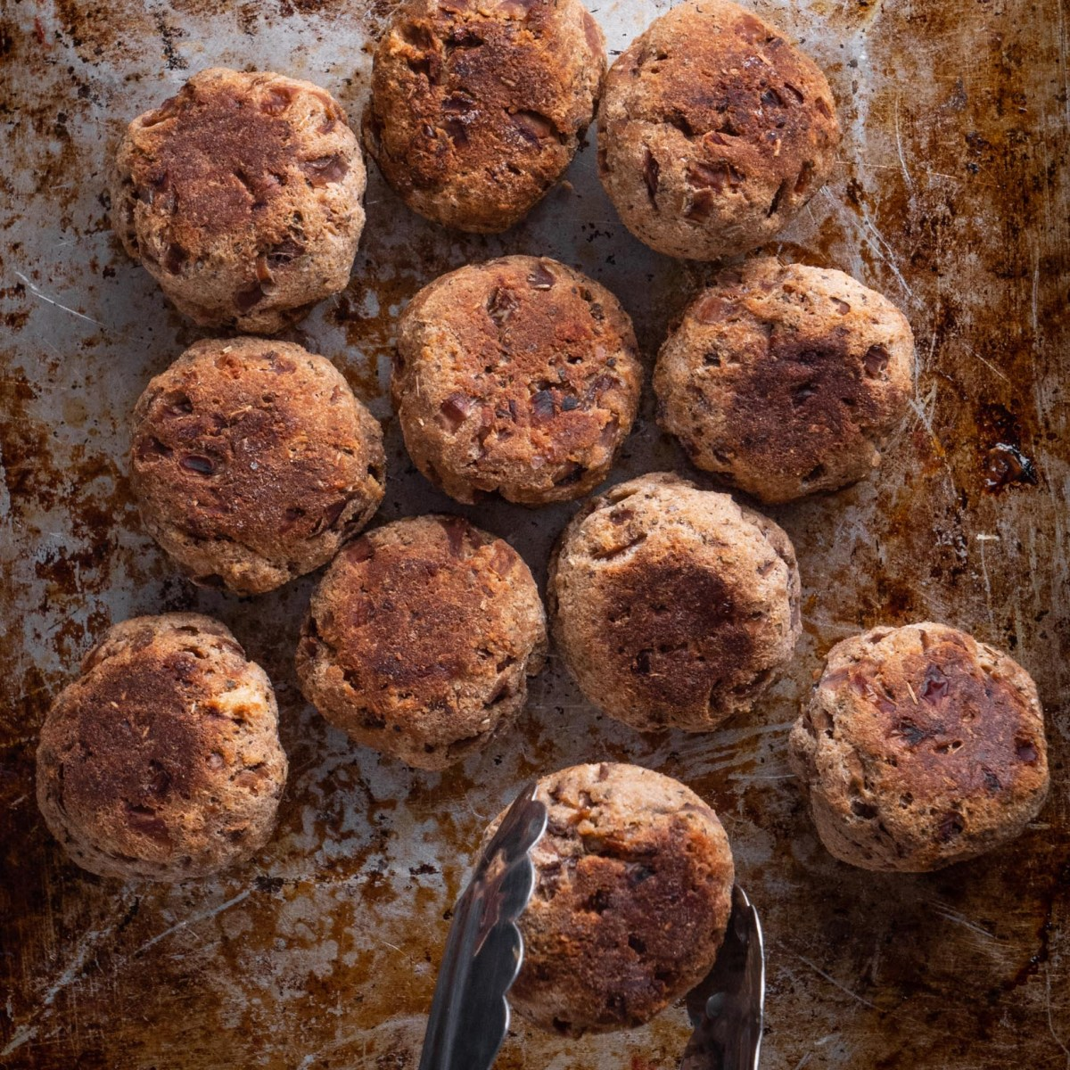vegan sage and onion stuffing balls on a rustic metal baking tray
