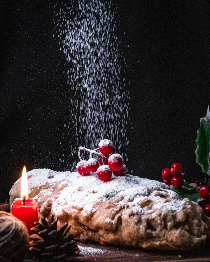 german fruit loaf topped with red berries and being sprinjled with powdered sugar like snow against black background