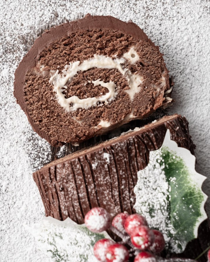 slice of swiss roll next to rest of cake topped in chocolate ganache made to resemble tree bark and decorated with holly sprig and berries