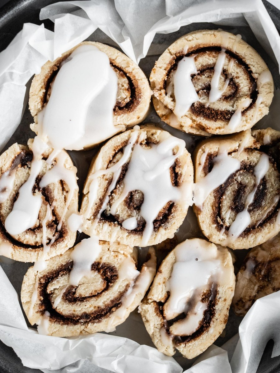 cinnamon rolls with brown swirls in bread rolls in round metal baking tin