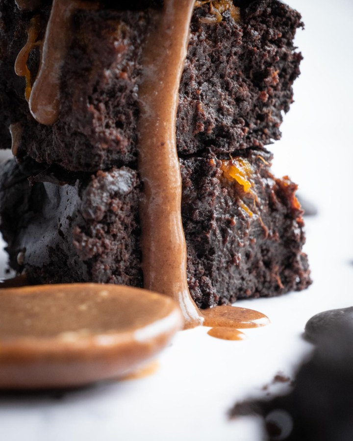 fudgy chocolate brownie on white table dripping down edges with runny nut butter next to wooden spoon