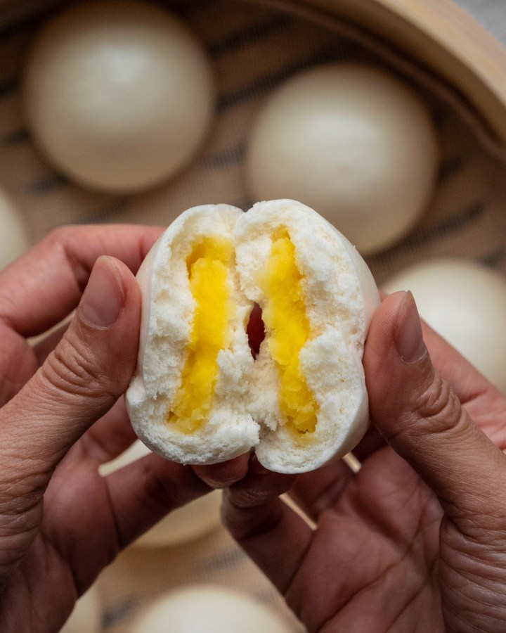 hands breaking apart soft and fluffy white steamed chinese bread bun revealing sweet yellow filling inside