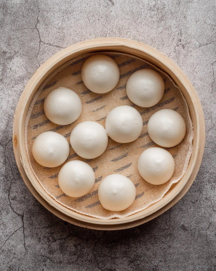 several steamed chinese custard buns in bambbo steamer on cracked concrete floor