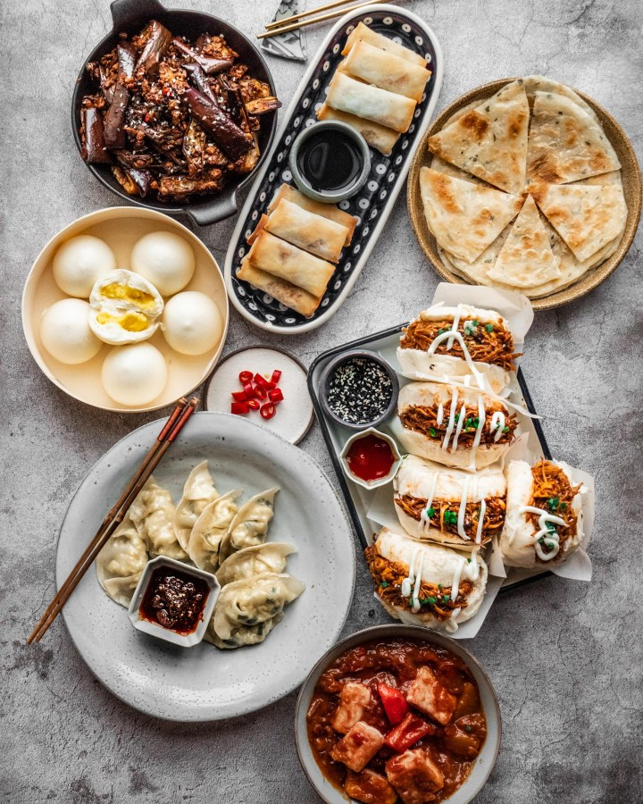 chinese food banquet with bao buns, fried rice, custard baozi, dumplings, aubergine and spring rolls