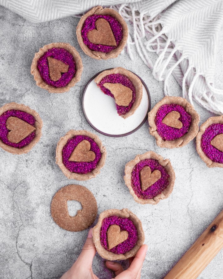 flatlay jam tarts with pink jam topped with pastry love hearts on white grey stone surface next to vintage grey and white wool cloth