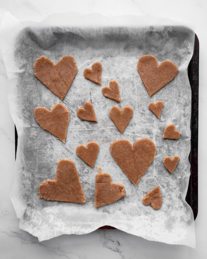 love heart shaped pastries on baking tray lined with white greaseproof paper