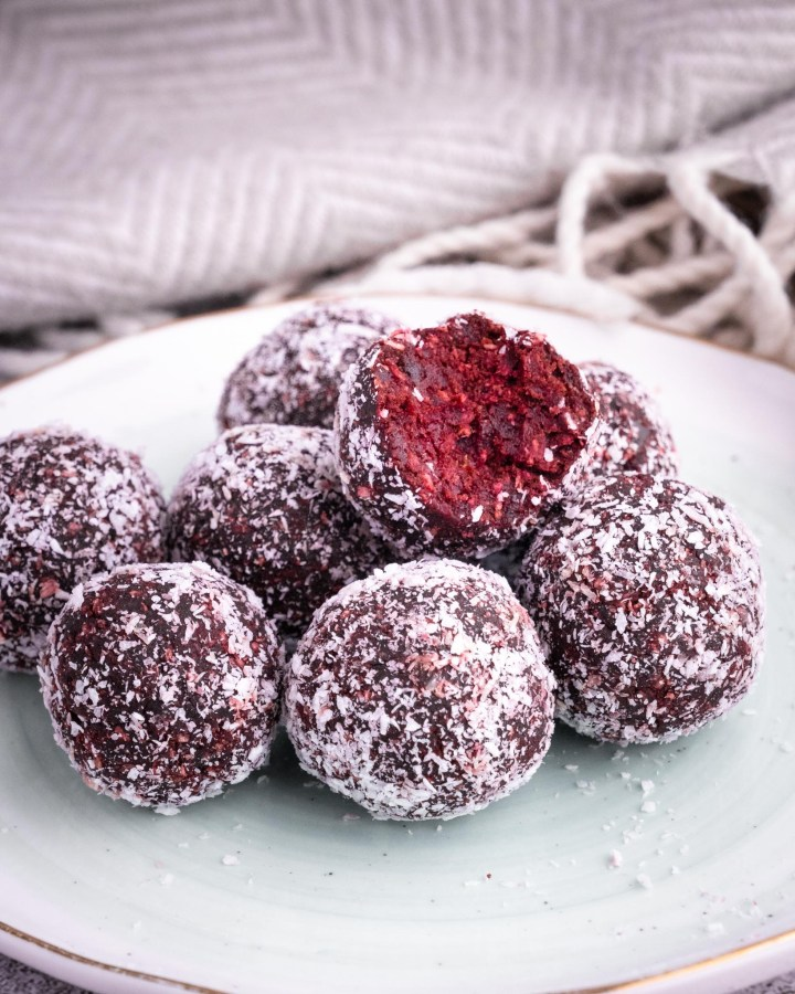 no-bake red velvet cake balls stacked on each other dusted in shredded coconut on white pottery plate with grey pinstripe crumpled cloth