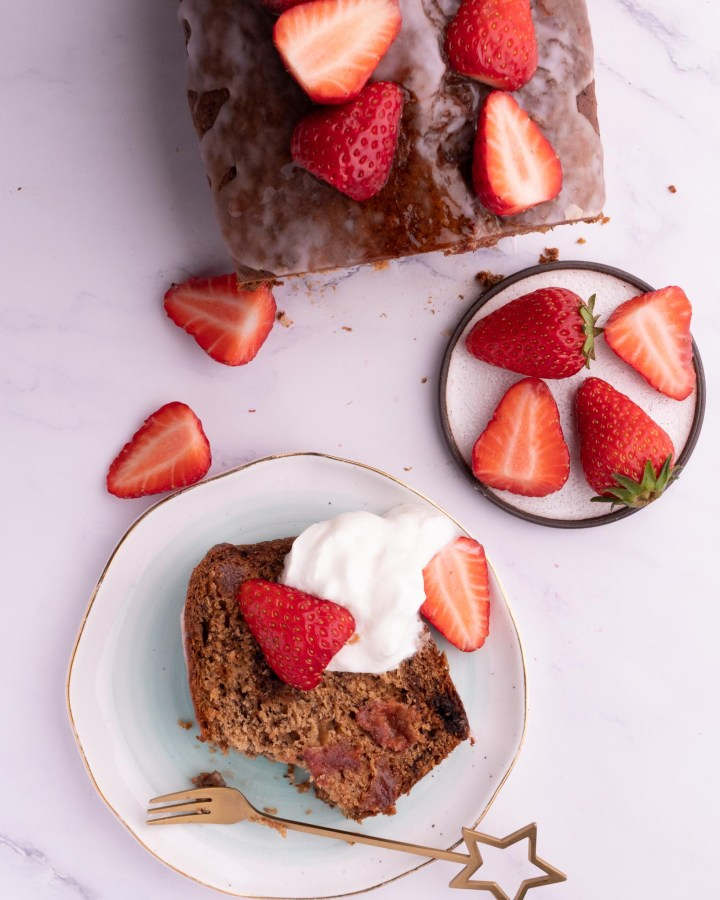 flatlay slice of strawberry banana bread on small plate next to large load topped with strawberries and cream