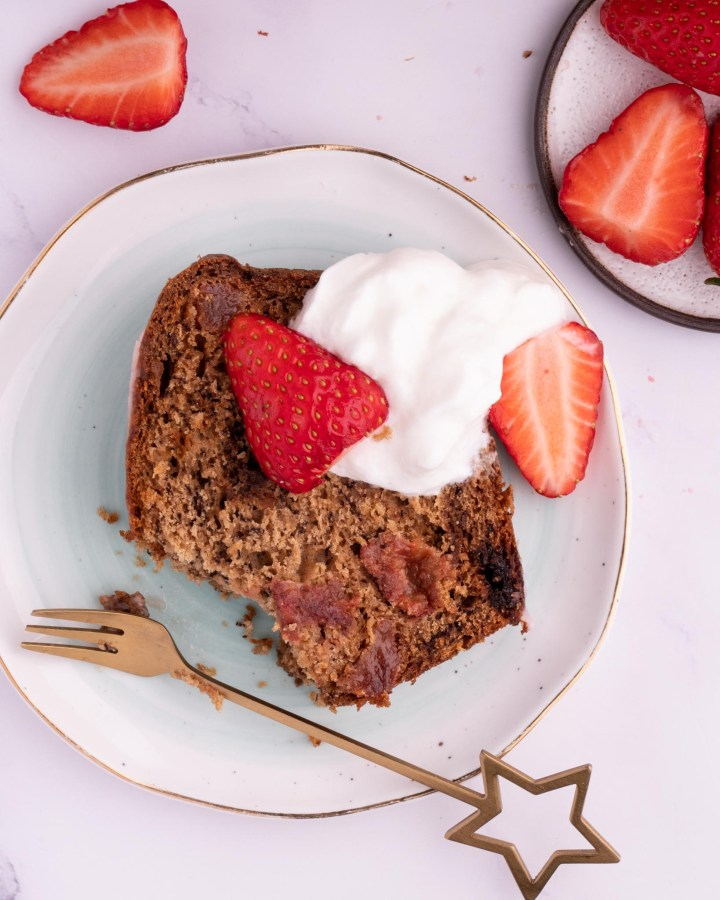 gluten-free loaf cake slice topped with whipped cream and strawberries on white marble table