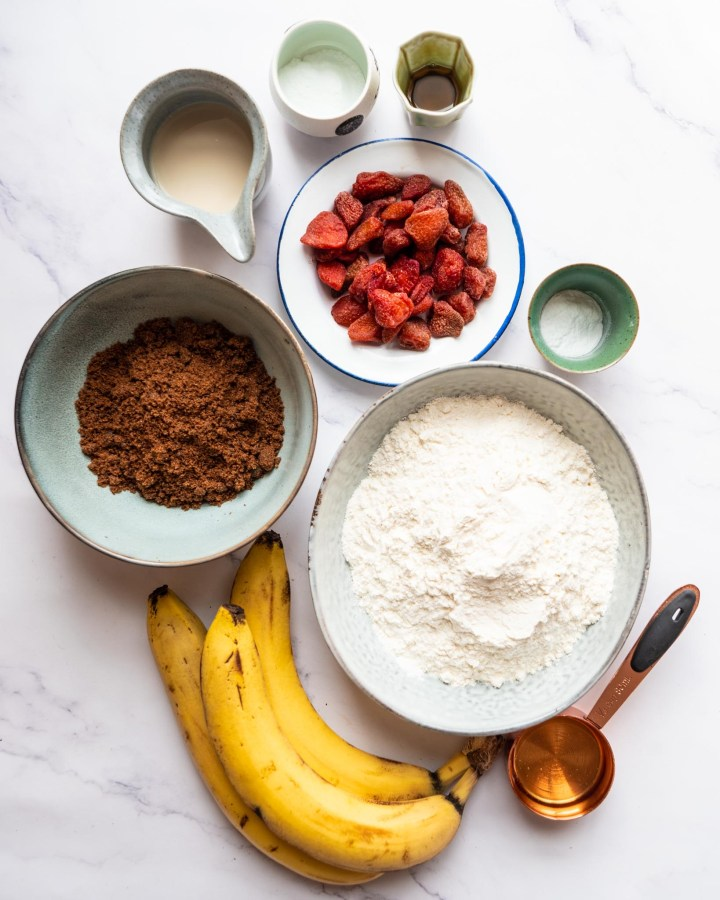 collection of ingredients required to make banana bread in rustic bowls on white surface