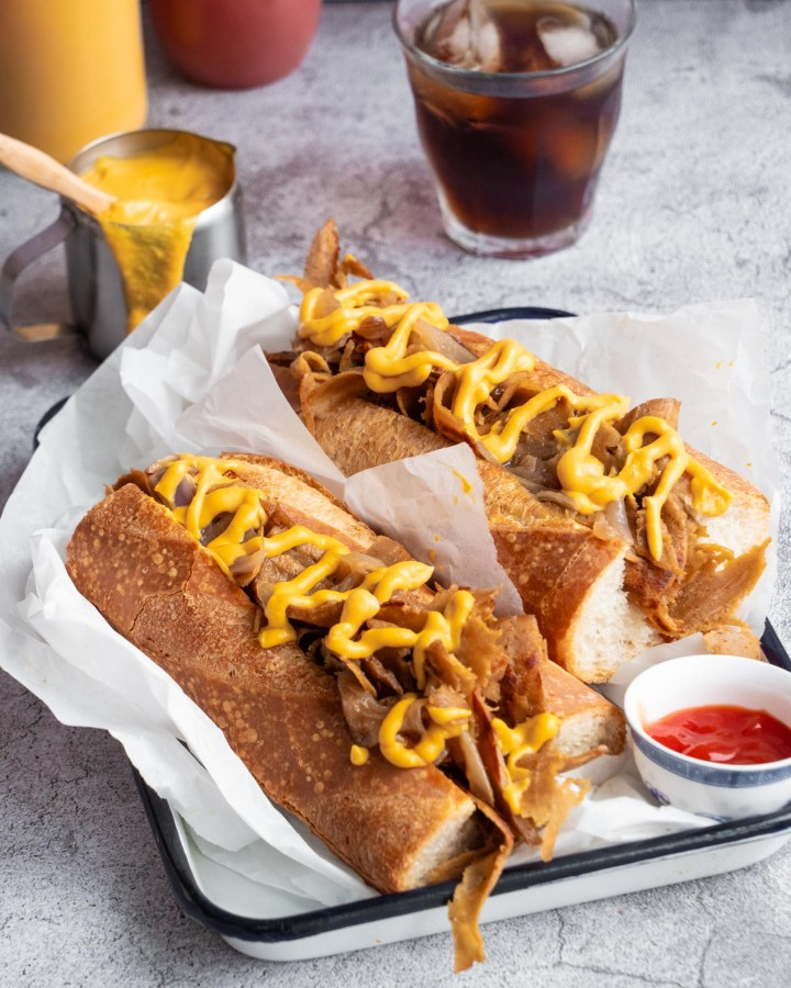 vegan seitan sandwich philly cheesesteak with vegan nacho cheese squirted on top in white enamel tray next to metal pot of ketchup