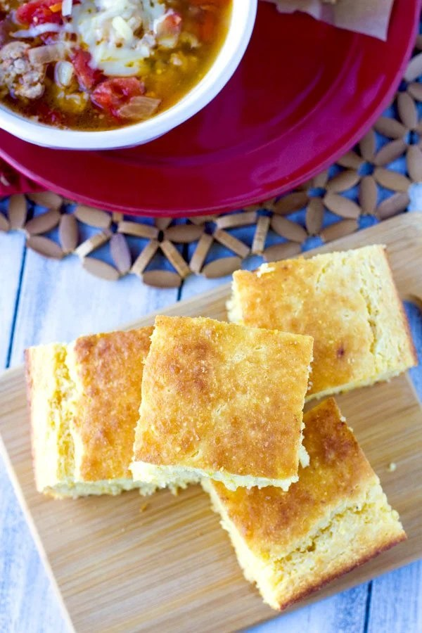 Overhead picture of pieces of cornbread with some soup in the background.