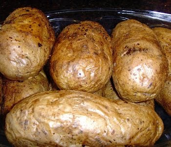 The finished oven baked potatoes on a serving bowl.