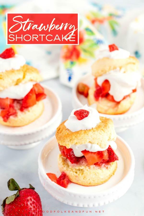 3 Strawberry shortcakes on white pedestals.