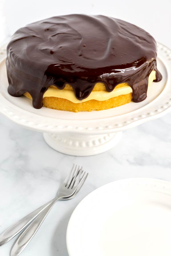 The finished Boston Cream Pie on a pedestal with 2 plates and 2 spoons.