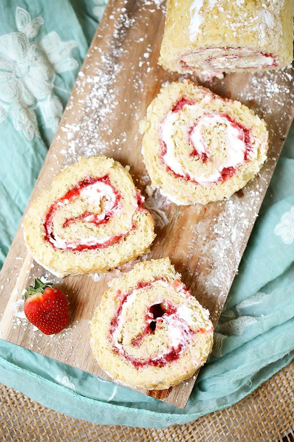 3 Slices of this strawberry shortcake roll on a wooden cutting board.