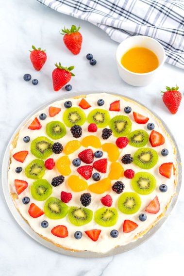 Fruit pizza in a pizza pan with fruit and a citrus glaze surrounding it.