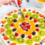 The citrus glaze being drizzles over the fruit pizza.