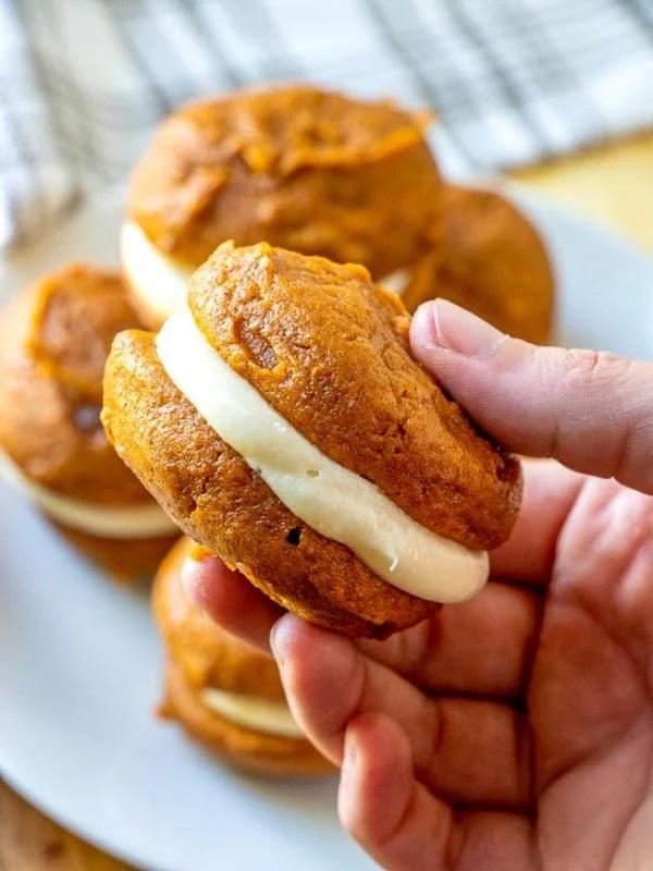 A hand holding a pumpkin whoopie pie.
