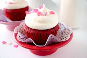 The best homemade Red Velvet Cupcakes on a red pedestal and paper doily decorated for Valentine's Day.