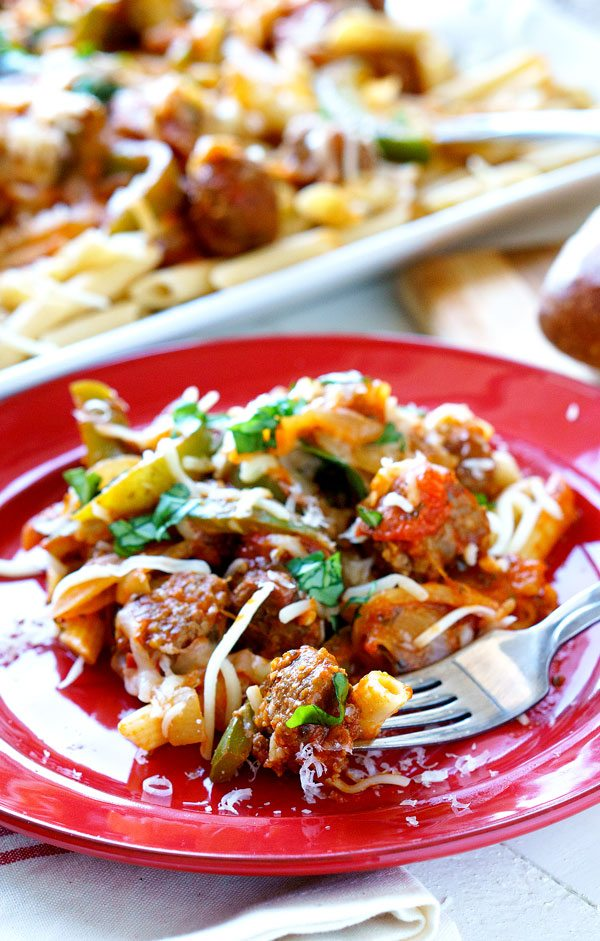 A fork digging into this sausage and peppers pasta.