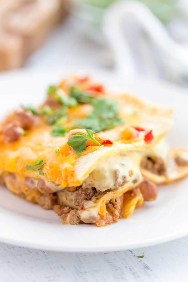 Mexican Lasagna with stacked tortillas, seasoned ground beef, beans, Rotel tomatoes, and cheese!