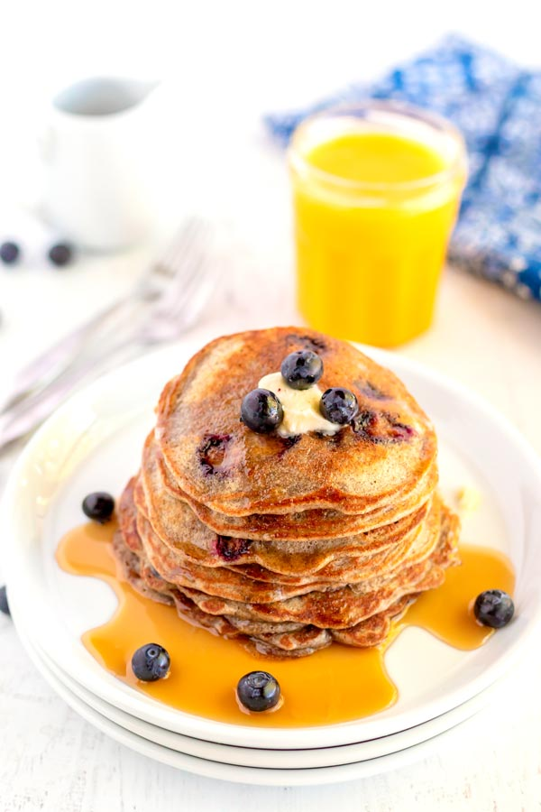 A stack of pancakes with butter, a drizzle of syrup, and fresh blueberries.
