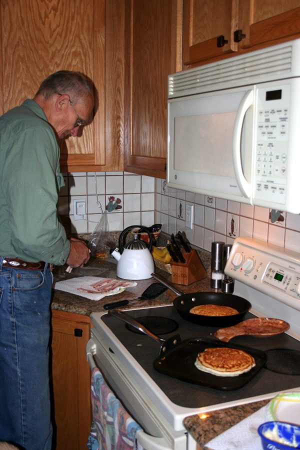 "My dad at the stove making his famous ""hotcakes""."