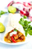 A chicken fajitas with sour cream, cheese, and salsa.