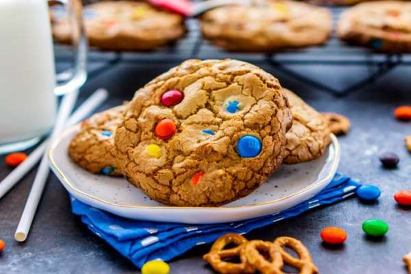 Cookies on a plate with pretzels and M&Ms around it.