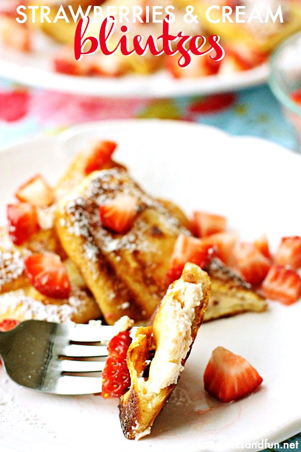 A close-up of a bite of Strawberries and Philly Cream Cheese Blintzes stuffed with a strawberry cream cheese filling, pan-fried and dusted with powdered sugar