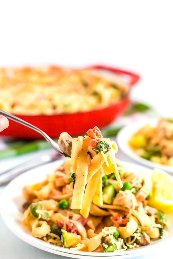 A fork listing up pasta that's covered in cream sauce and loaded with vegetables.