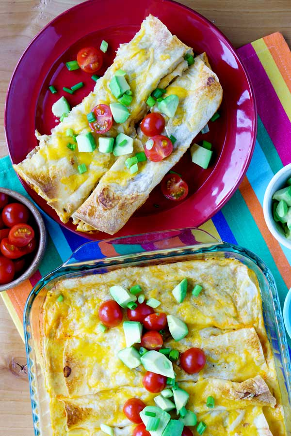Overhead shot of breakfast enchiladas on a plate and in a casserole dish.