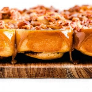 Finished sticky buns with bacon and caramel glaze with text overlay for Pinterest.