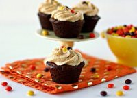 Brownie cupcake on an orange napkin with peanut butter frosting.