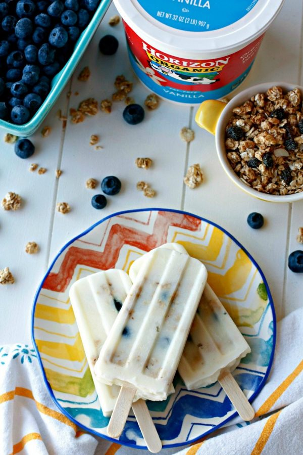 An overhead picture of 3 popsicles on a plate with granola and blueberries sprinkled around the plate.