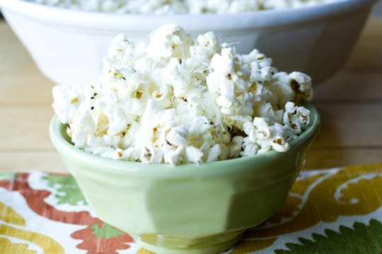 A close up picture of Truffle Popcorn with Parmesan in a green bowl.