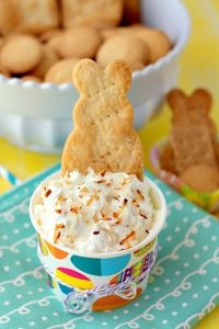 A close up of Coconut Cream Pie Cheesecake Dip in a small bowl with a bunny crakcer