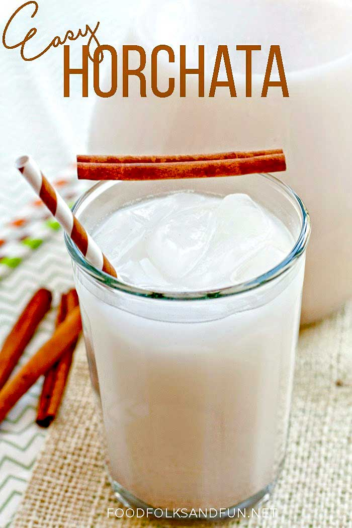 Homemade horchata in a glass garnished with cinnamon sticks.