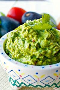 Guacamole in a serving bowl. with cilantro on top.