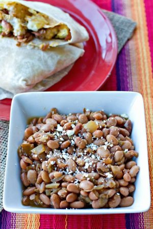 Crock Pot Green Chile Pinto Beans Recipe – this is my all-time favorite pinto beans recipe for stuffing into burritos. These beans are easy to make and so tasty!