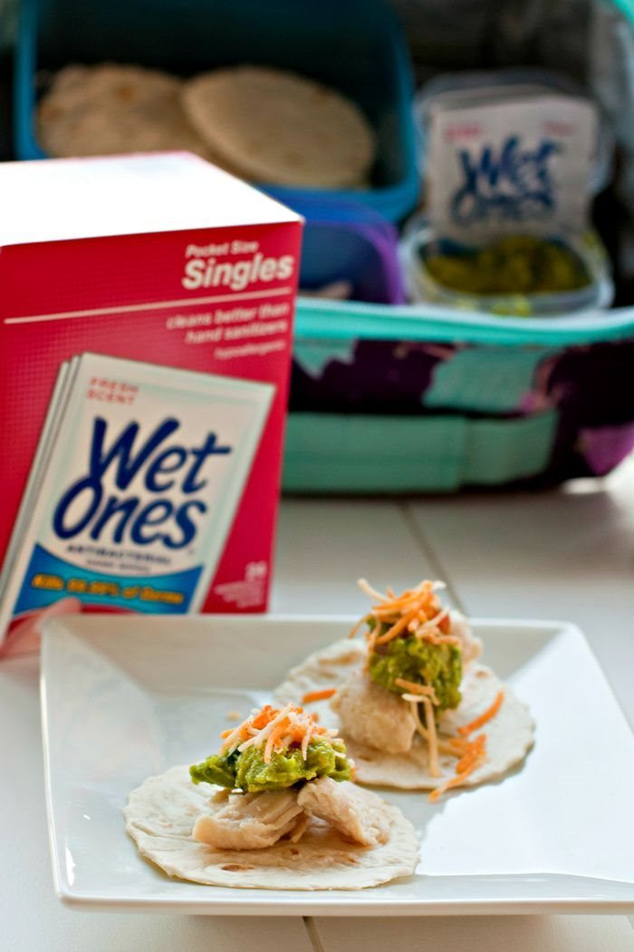 Lunch box tacos on a plate with wet wipes in the background