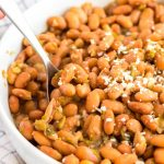 Pinto beans with green chile in a large bowl with serving spoon.