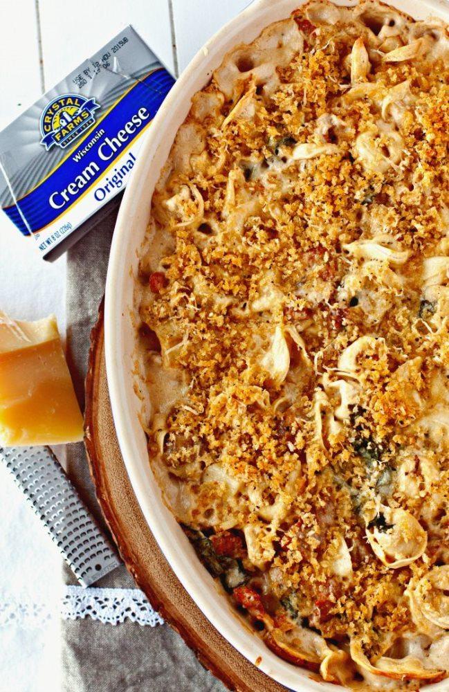 Creamy Tuscan Tortellini Bake in a casserole dish alongside ingredients needed to make it