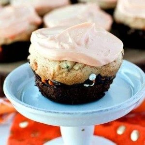 A brookie cupcake with frosting on a cake stand