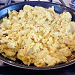 A close-up of scrambled eggs in a skillet