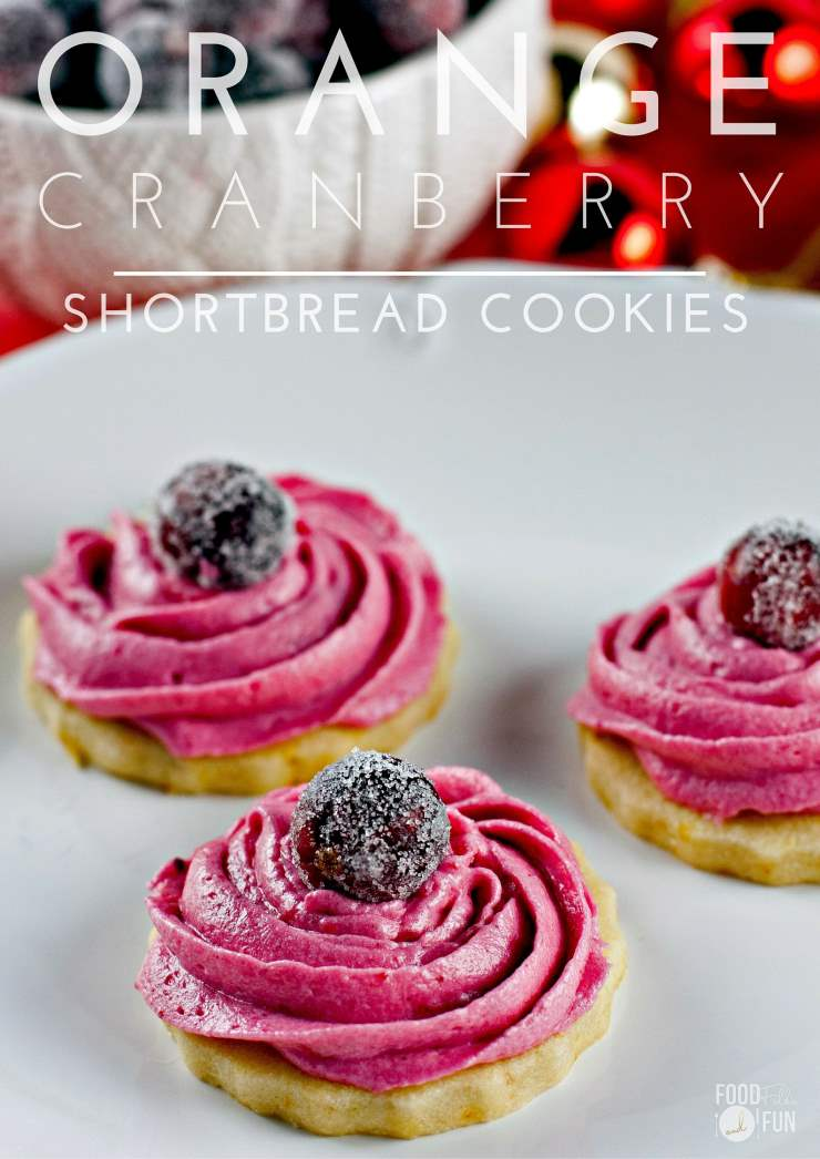3 Orange shortbread cookies with cranberry frosting on a plate.