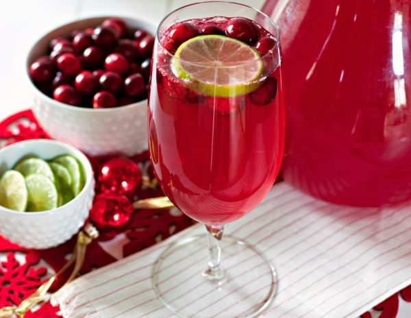 Cranberry mocktail garnished with fresh cranberries and lime slices.