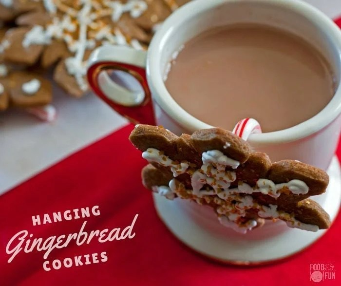 Gingerbread cookie with a small candy cane attached, and hanging from a cup of cocoa.